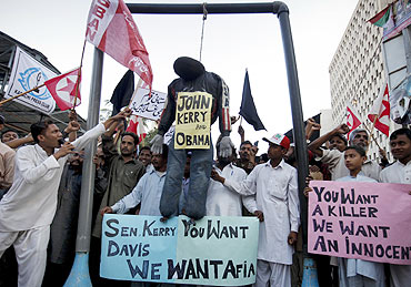 Pak protestors hang an effigy of US President Barack Obama and Senator John Kerry during a protest