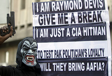 A supporter of a political party poses with a mask and toy gun during a protest against Davis