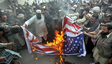 Protestors in Pakistan burn a US flag during a rally against Davis near the US consulate