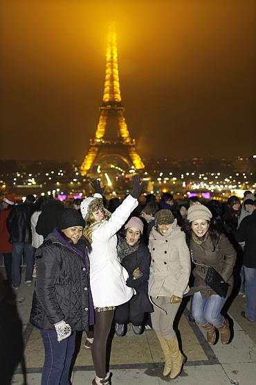 Revellers celebrate the New Year in front of the Eiffel tower in Paris