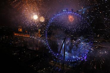 Fireworks explode beside the London Eye and The Houses of Parliament on the River Thames during New Year celebrations in London