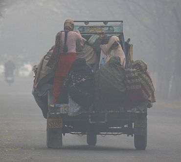 Women travel on the back of a vehicle on a cold and foggy day near Chhuni village in Punjab