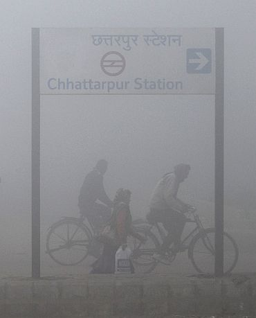People ride bicycles on a foggy morning in New Delhi