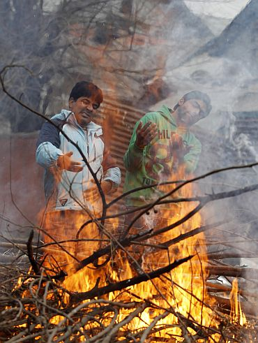 Kashmiri people warm their hands at a fire on a cold day in Srinagar