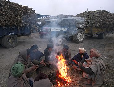 Farmers warm themselves by a fire as they wait to sell their sugarcane crop at a mill on a cold morning at Morinda in Punjab
