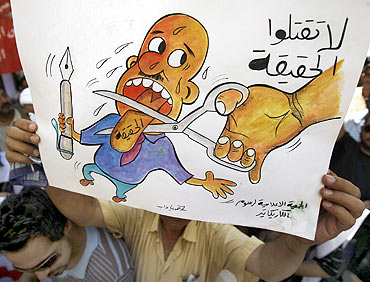 A protester holds up a cartoon sign that reads 'Don't kill the truth' during a protest at Baghdad