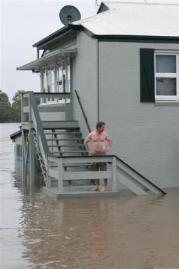 Owner Brett Jensen looks on as he stands next to his restaurant affected by floods in Bundaberg, Queensland
