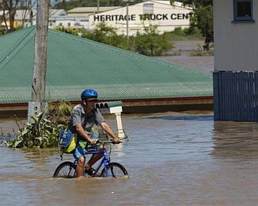 A man rides his bicycle on a street affected by flood waters in Bundaberg, Queensland