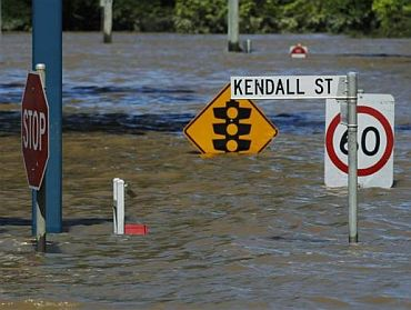 Street signs submerged in flood waters are seen in Kendall Street in Bundaberg, Queensland