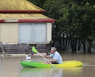 Christopher Roth rows down a flooded street in Bundaberg, affected by floods in Queensland