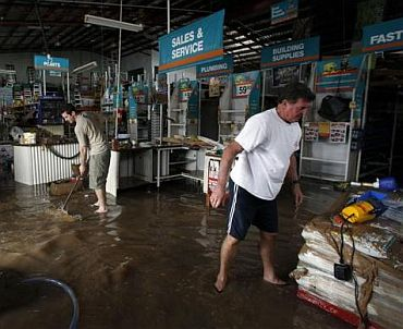 Workers of a hardware store start to clean up after being affected by flooded waters in Bundaberg, Queensland