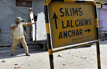 A policeman uses a sling against stone and brick throwing Kashmiri protesters during an anti-India protest on the outskirts of Srinagar