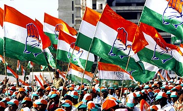 Supporters hold party flags during a Congress election campaign rally in Mumbai