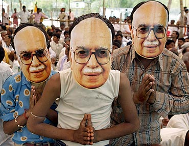BJP supporters wear masks of senior leader Lal Krishna Advani during an election campaign rally at Biaora in Madhya Pradesh