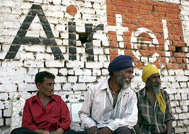 Men sit in front of a wall advertising Bharti Airtel at a roadside in Ahmedabad