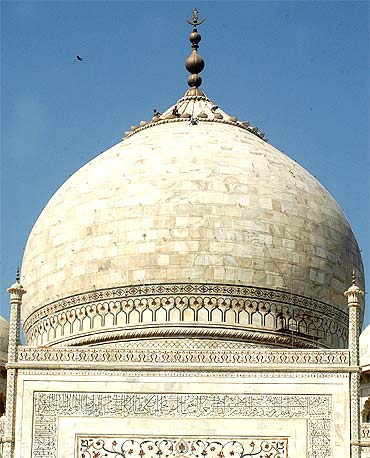 Workers repair a dome of the Taj Mahal