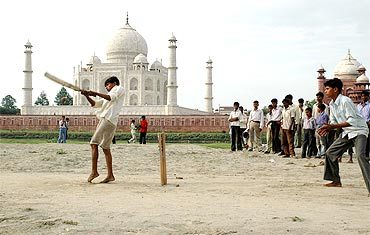 Children play cricket on the banks of river Yamuna, behind the Taj Mahal