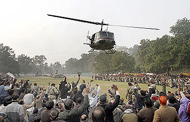 Supporters wave at a helicopter carrying Taseer's body