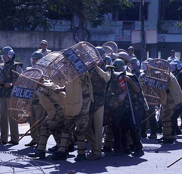 Policemen take cover as pro-Telangana activists throw stones