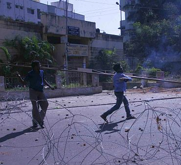 University students pelt stones on policemen during a protest