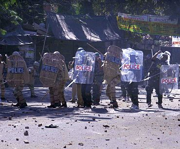 Policemen take cover as an irate mob pelts stones on them