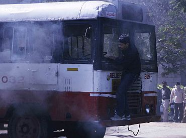 A protestor boards a damaged bus