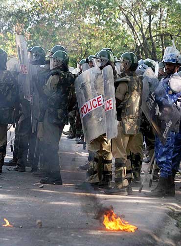Policemen stand guard as violence erupts in Hyderabad over the Telangana issue