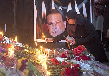 A woman lights a candle next to an image of the governor of Punjab Salman Taseer near the site of his assassination, in Islamabad