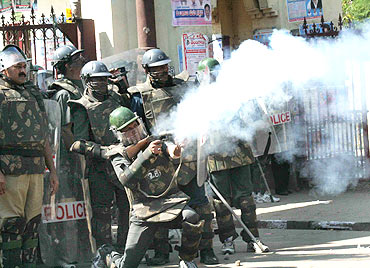 A policeman lobs tear gas shells to disperse protestors at the university campus in Hyderabad on Friday