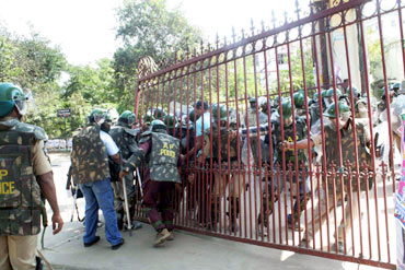 Security forces try to close the main entrance gate of the Osmania varsity