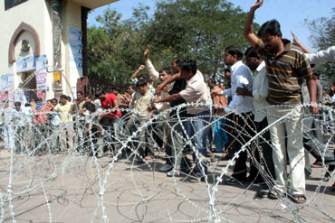 Pro-Telangana students try to break through a barbed wire at the university gate on