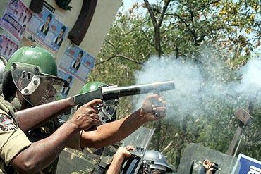 A policeman lobs a tear gas shell near Osmania campus on Friday