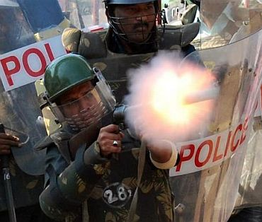 Policemen fire a teargas shell to disperse protestors