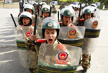 Chinese policemen take part in anti-riot training at a military base