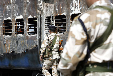 Rapid Action Force personnel stand guard besides a burnt carriage of a Samjhauta Express train near Panipat on February 19, 2007