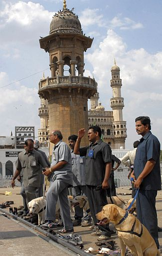 Policemen use sniffer dogs to inspect the blast site