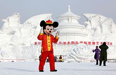 A man dressed as Mickey Mouse poses in front of a snow sculpture at a park