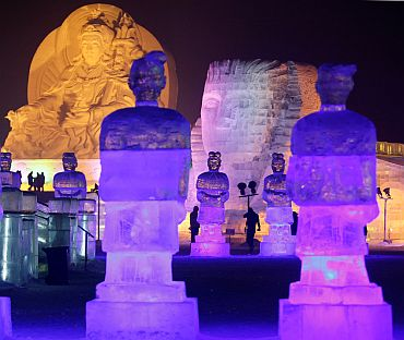 After nightfall, people visit ice sculptures at a park in Harbin