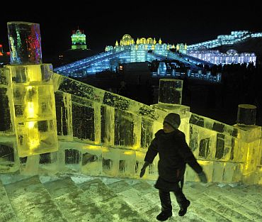 A visitor climbs on icy stairs on an ice sculpture