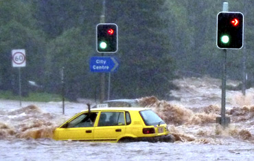 A passenger in a car waves for assistance as a flash flood sweeps across an intersection in Toowoomba, 105 km west of Brisbane