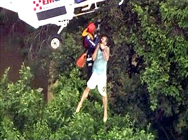 A man is lifted up to a helicopter in the flooded town of Toowoomba, west of Brisbane, in this still image taken from video