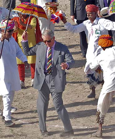 Britain's Prince Charles dances with villagers at Tolasar village near Jodhpur