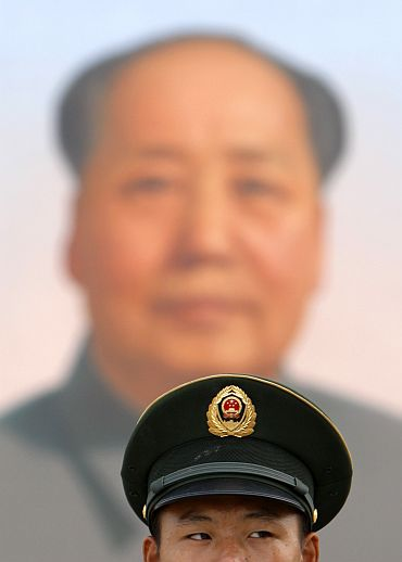 A guard stands beneath the portrait of the late China's Chairman Mao Zedong in Tiananmen Square in Beijing