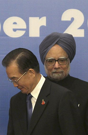 File photo shows China's Premier Wen Jiabao walking past India's Prime Minister Manmohan Singh ahead of a photo opportunity as part of the 5th East Asia Summit in Hanoi