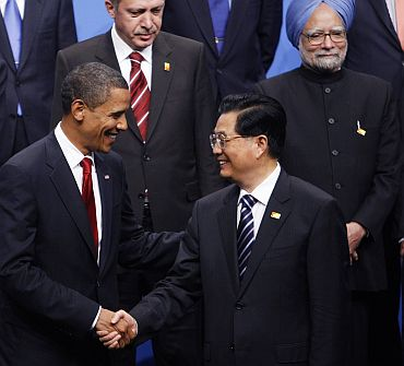 File photo shows US President Barack Obama shaking hands with China's President Hu Jintao as India's Prime Minister Manmohan Singh look on at rear, at the G20 Summit in Pittsburgh