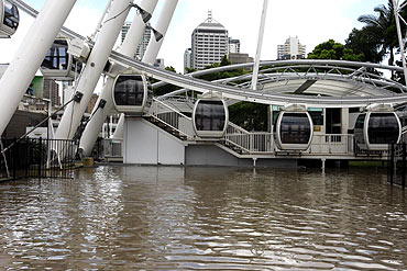 Flood waters are seen in front of the Wheel of Brisbane ferris wheel