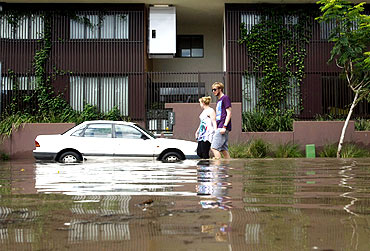 A couple walks past a flooded apartment building in Brisbane