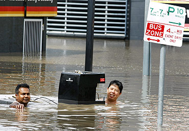Shopkeepers salvage a coffee machine from their flooded shop in the Brisbane suburb of Milton