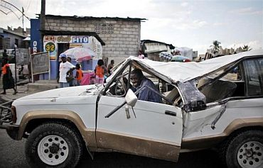 A man smiles as he drives a damage vehicle on a busy street in Port-au-Prince