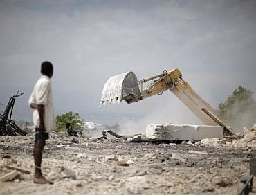 A boy looks at a bulldozer clear rubble from a destroyed church in Port-au-Prince